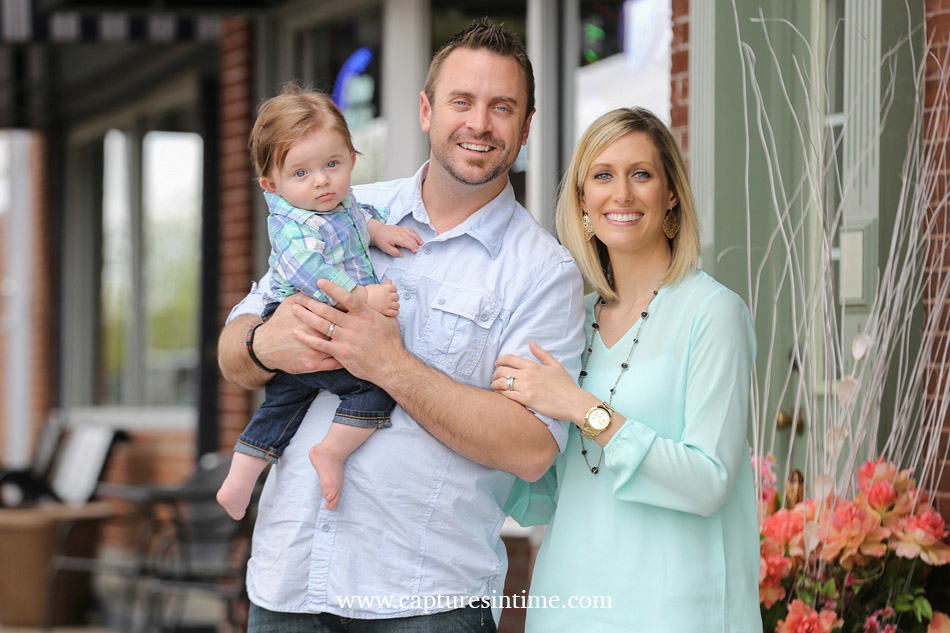 baby photography kansas city mom dad and red head baby boy on Main street in Blue Springs