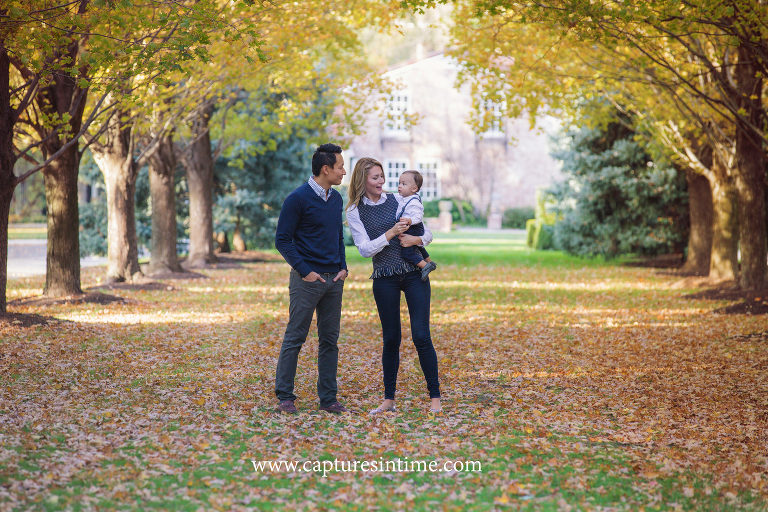 family of three mom dad and baby in fall trees