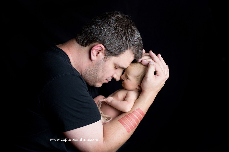 kansas city newborn baby photography dad with arm tattoo nose to nose with his newborn baby girl