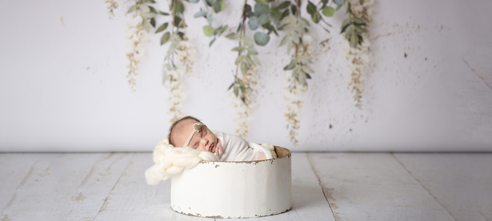 baby laying in bowl in front of leaf backdrop