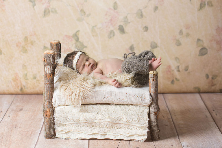 newborn girl in birch bed floral backdrop