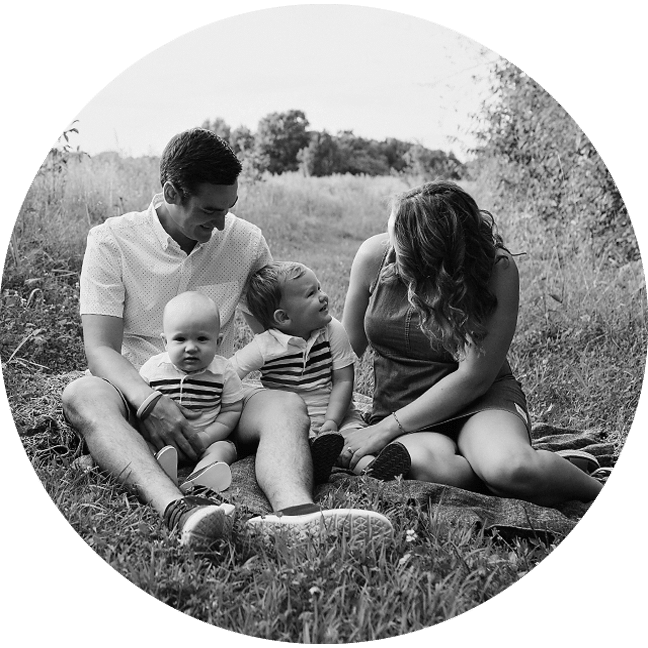 family sitting in the grass black and white